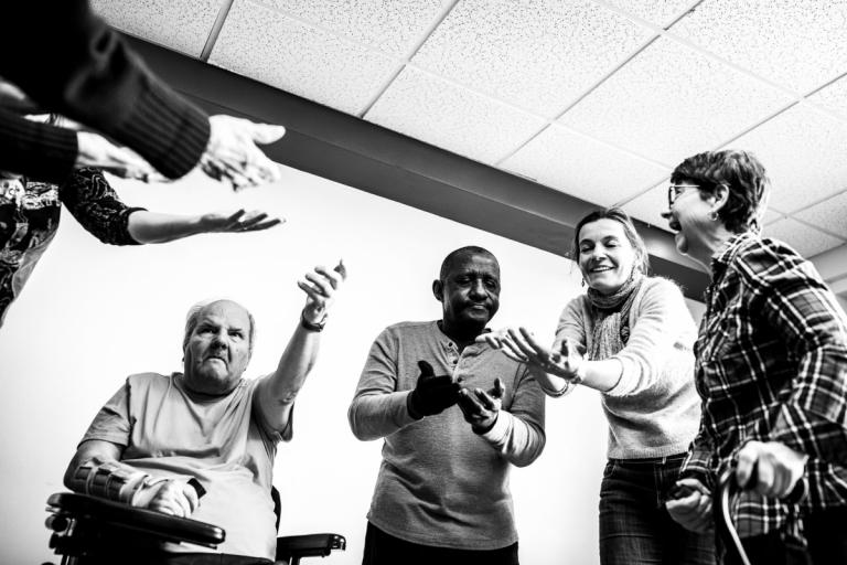 Photo en noir et blanc d'un groupe de personnes ayant différentes limitation fonctionnelle font un atelier de théâtre.